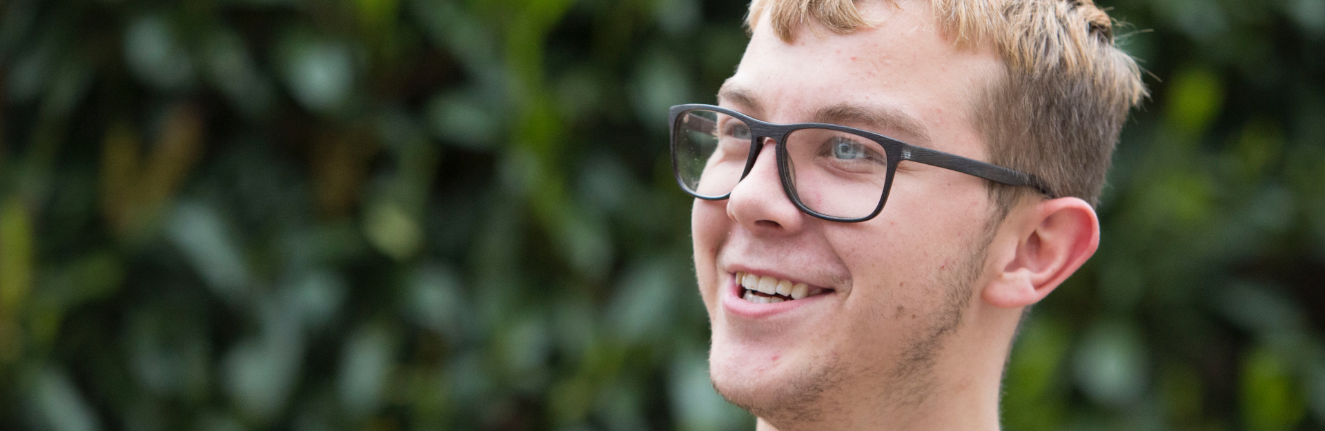 A person in glasses smiling, with a hedge behind them